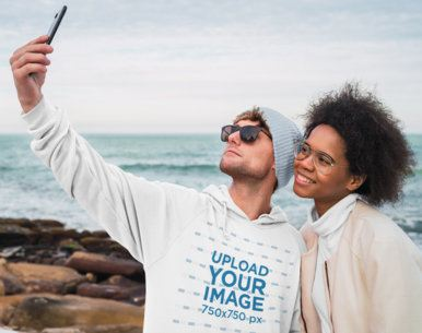 Pullover Hoodie Mockup of a Man Taking a Selfie by the Beach 39568-r-el2