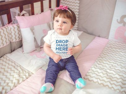 Beautiful Baby Girl Sitting In Her Crib While Wearing a Onesie 13955