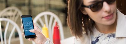 Black iPhone 6 Being Held By Girl With Sunglasses At A Diner Restaurant Mockup a13993wide
