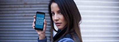 Mockup Of A Beautiful Woman In An Urban Environment Looking At The Camera While Showing An iPhone 6 In Portrait Position a14037w
