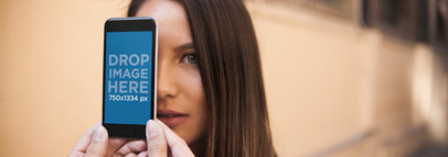 Gorgeous Girl Hiding Behind An Black iPhone Held By Hands Mockup a14034w