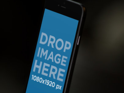 Angled Blurred Black iPhone 6 In Portrait Position Close Up Against Dark Background Mockup a12707