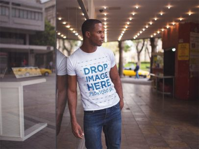 Young Black Man Wearing a Tshirt While Lying Against a Shop Window in the Street Mockup a14229