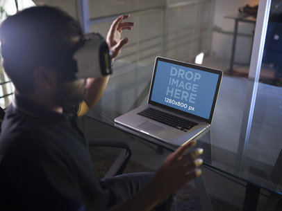 Mockup of a Young Man Wearing an Oculus Gear VR Device While His Macbook pro Is on the Desk a14246
