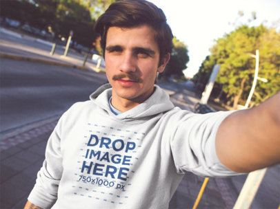 Selfie Mockup of a Young White Man With Moustache Wearing a Pullover Hoodie While In The City a13610
