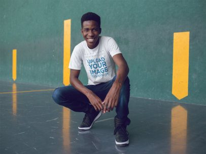 Smiling Young Black Man Crouching While Wearing a Round Neck Tshirt a14256