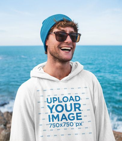 Mockup of a Happy Man with a Hoodie Standing by the Beach 40478-r-el2