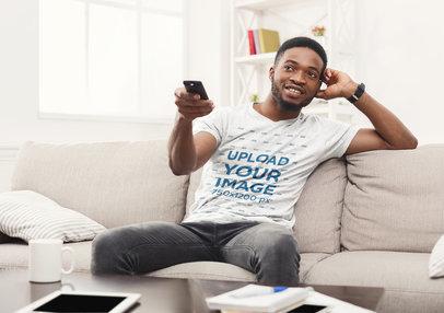 T-Shirt Mockup of a Man Watching TV at Home 43211-r-el2