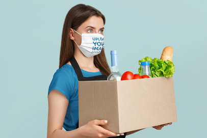 Face Mask Mockup of a Woman with a Box of Groceries in a Studio 44177-r-el2