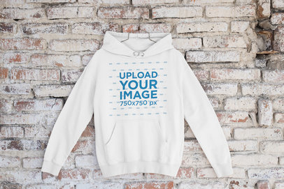 Mockup of a Pullover Hoodie Placed on a Hanger by a Brick Wall m434
