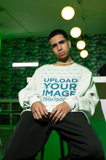 Sweatshirt Mockup Featuring a Serious Young Man Posing in a Room With a Green Light m573