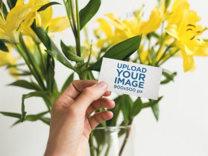 Business Card Mockup Held Next to Yellow Flowers a15006