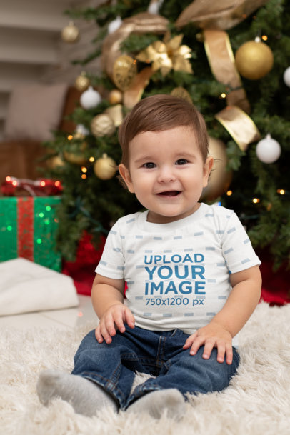 T-Shirt Mockup Featuring a Baby in Front of a Christmas Tree M1007
