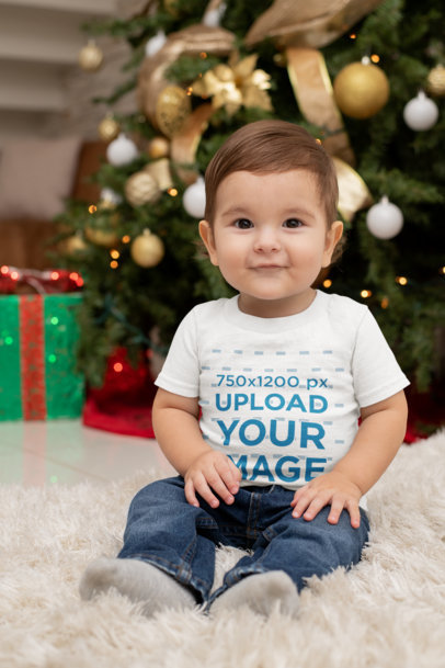 T-Shirt Mockup Featuring a Baby Boy Sitting by a Christmas Tree m1008