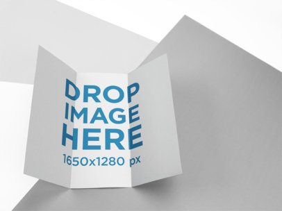 Open Trifold Brochure Mockup Lying on a Multicolor Surface a15211