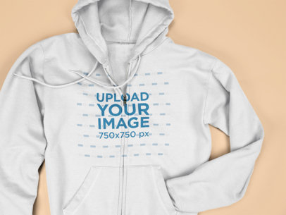 Mockup of a Full Zip Hoodie Hiding a Sleeve Lying on a Flat Surface a15241