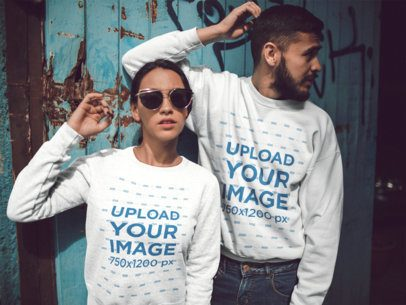 Hispanic Couple Wearing Different Crewneck Sweatshirts Mockup While Standing Against an Old Door a15532
