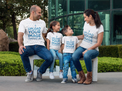 Couple With Kids Wearing Different Tees Mockup Sitting on a Bench While Outdoors a15484