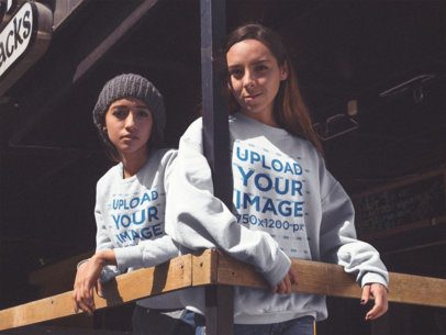 Two Girlfriends Hanging Out and Wearing Different Crewneck Sweatshirts Mockup at a Bar Terrace a15582