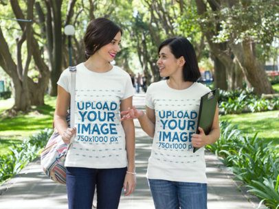 Two Hispanic Girls Wearing Different Tees Mockup While Walking and Talking at the Park a15658