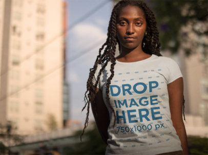 Black Girl Wearing a Tshirt Template While Standing Against Blurry Buildings in the City a15547