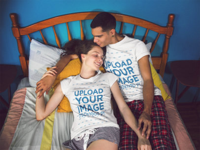 Young Couple Lying on Their Bed Holding Hands and Smiling While Wearing Tshirts Template with Different Designs a15713