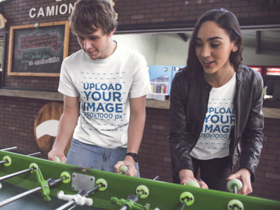 Young Couple Playing Foosball and Wearing Different Round Neck Tees Mockup a15697