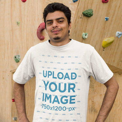 Young Man Wearing a Round Neck Tee Mockup while Standing Against a Climbing Wall a15524