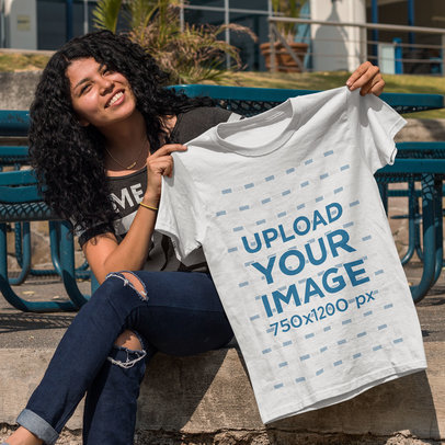 Young Happy Customer Showing a T-Shirt Template While Sitting Down Outdoors a15654