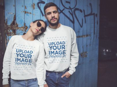 Happy Couple Wearing Different Crewneck Sweatshirts Mockup While Standing Against a Blue Door a15804