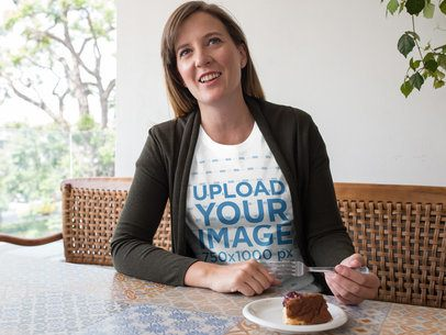 Smiling Woman Wearing a Round Neck T-Shirt Mockup While Eating Dessert at a Restaurant a15773