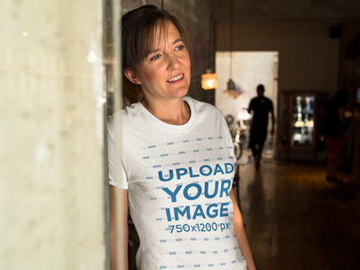 Smiling Middle Aged Woman Lying Against a Wall While Wearing a T-Shirt a15776