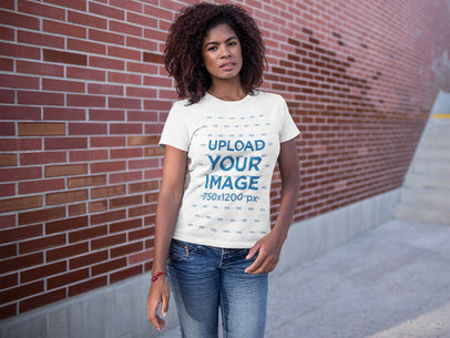 T-Shirt Mockup Being Worn by a Black Woman Standing Near a Bricks Wall a15812