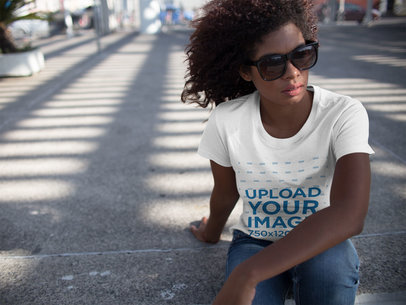 Woman Wearing Sunglasses and a T-Shirt Template While Facing the Wind Sitting Down on the Street a15829