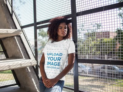Black Girl Wearing a Tshirt Mockup While Lying Against a Fence a15809