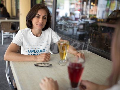 Mockup of a T-Shirt Being Worn by a Middle Aged Woman While Talking to a Friend in a Cafe a15863