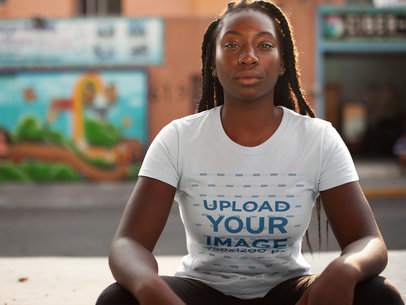 Young Black Woman with Dreadlocks Wearing a Round Neck T-Shirt Mockup While Sitting Down in the Street a15943