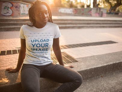 Young Black Girl with Dreadlocks Sitting Down Near a Skate Park While Wearing a Round Neck Tee Template a15946
