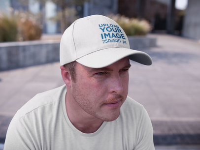 White Guy Wearing a Dad Hat Mockup While Sitting Down Outdoors a15878