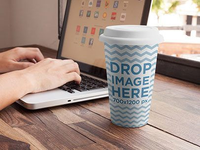 Coffee Cup Mockup Featuring a Woman Using a Macbook Pro at a Café a6965