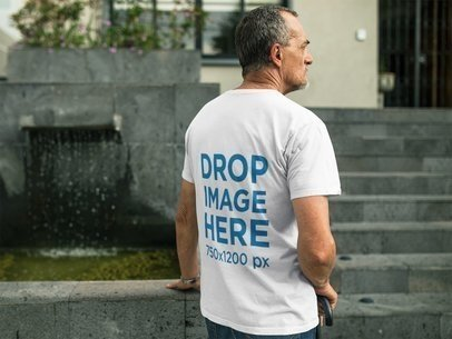 Elder Man Wearing a Round Neck Tee Mockup Standing Near a Fountain a10985b