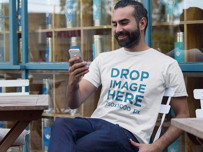 T-Shirt Mockup of a Man Using His iPhone Outdoors a8234