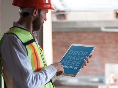 Mockup of a Man Using His iPad in Portrait Mode and Wearing a Construction Vest 12419