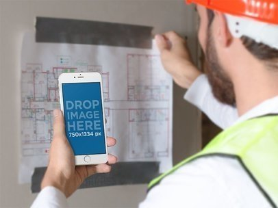 iPhone Mockup in Portrait Mode of a Man Looking at a Construction Plan 12425