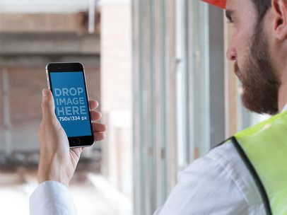 Over Shoulder Mockup of a Worker Holding His iPhone in Portrait Mode 12426