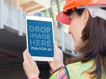 iPad Mockup in Portrait Position of a Female Worker with Blurry Background 12572