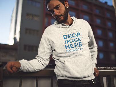Pullover Hoodie Mockup Featuring a Young Hipster Man Looking Over and Leaning on a Rail a12600