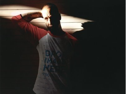 Man Wearing a Raglan T-Shirt with his Arm Back in a Dark Room b12616