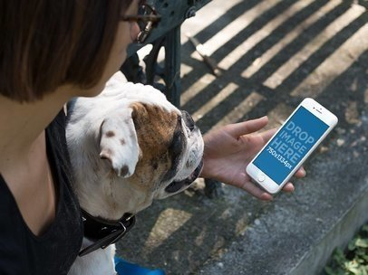 Mockup of a Woman with a Dog holding an iPhone in Portrait Position 12929