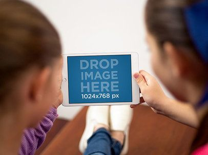 Two Little Girls Using an iPad Mini in Landscape View Mockup at their Home a12992